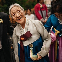 Korean grandmother smiles at camera during wedding reception.