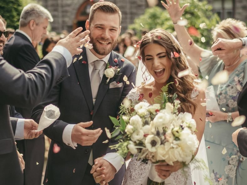 Bride and groom smile as they walk out of church after ceremony and flower petals are thrown at them.