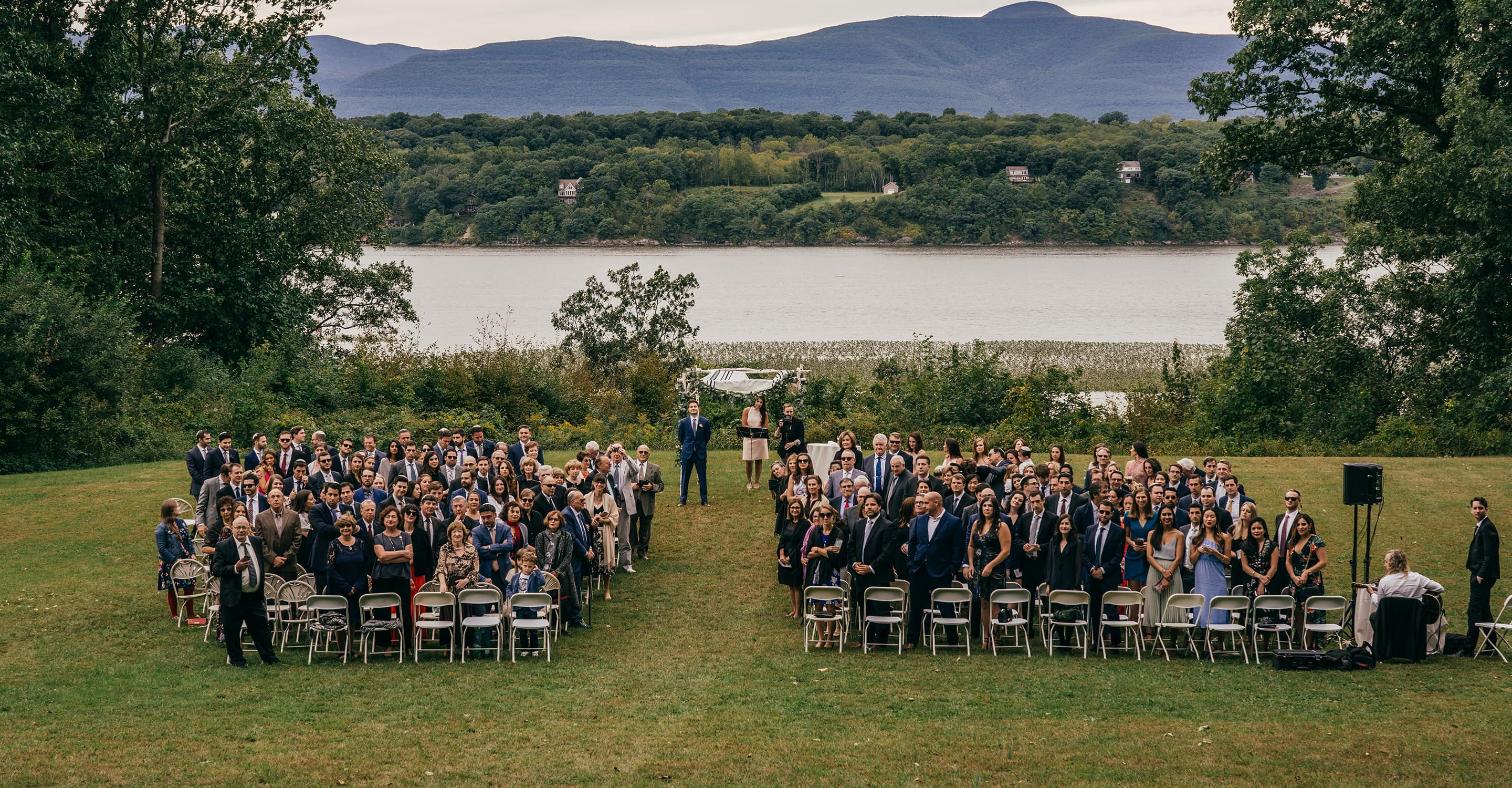 Wedding guests stand up and turn around as bride walks to wedding ceremony with Hudson River and mountains in background.