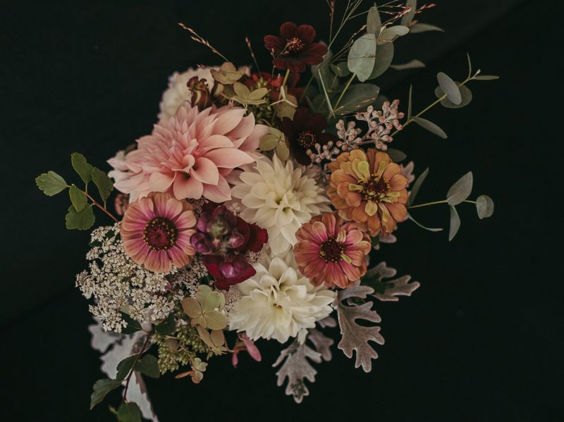 Top view of wedding bouquet with zinnias, dahlias, and other greenery against black background.