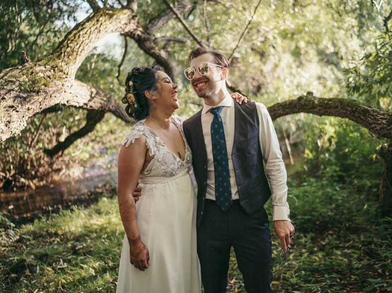 Bride and groom stand in Hudson Valley forest, laughing as groom wears bride's sunglasses.